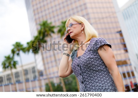 Close Up portrait Serious attractive business woman in glasses 65 years in the downtown talking with mobile phone, Lifestyle woman on phone, concept - businesswoman calling on the phone in street - stock photo