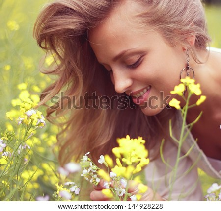 Close-up portrait, sexy blonde inhales the scent of flowers - stock photo