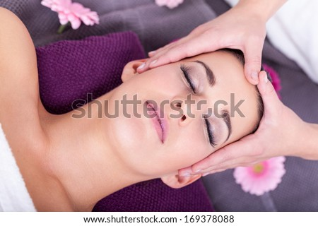 Close-up portrait shot from above of a young attractive brunette woman having a relaxing facial massage, in a fancy spa center, with scented candles and flowers