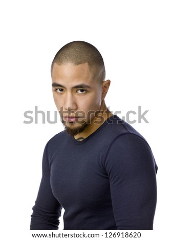 Close-up portrait shot of a serious young man with shaved head - stock photo