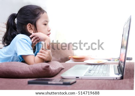 Close up portrait shot of asian little girl using laptop computer at home with copy space