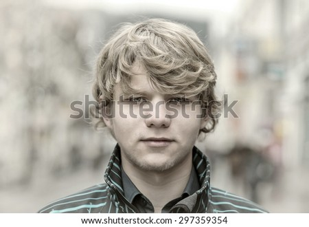 Close-up portrait teenager boy on the street - stock photo