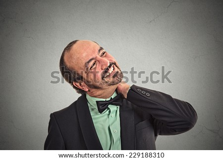 Close up portrait tired middle aged businessman executive with neck pain isolated on grey wall office background. Human face expression emotion, feeling. Long working hours body injury illness concept - stock photo