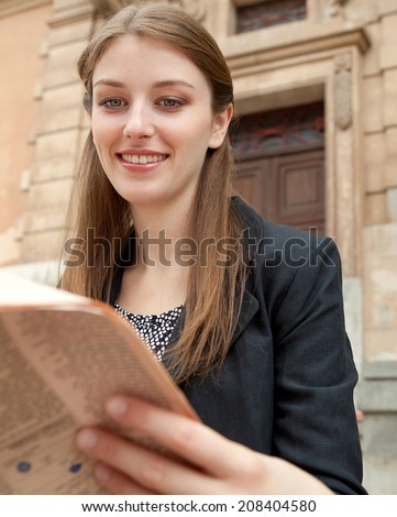 Close up portrait view of an attractive professional young woman sitting by a classic stone building in the city reading a financial newspaper, smiling outdoors. Business communications and news. - stock photo