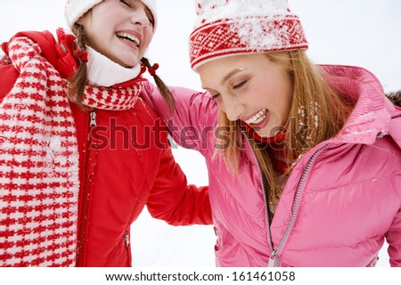Close up portrait view of two joyful young women friends having fun and laughing while in a skiing holiday in a white snow  landscape lake with big joy expressions and excitement, outdoors.
