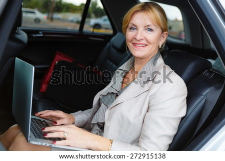 Close-up portrait with smiling happy old senior business woman 60-65 years, sitting in a car, holding her Laptop Computer pc in lap and type on the keyboard, looking to camera - stock photo