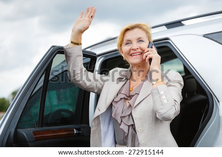 Close-up portrait with smiling happy old senior business woman 60-65 years, waving his hand and talking on the phone on car background - stock photo