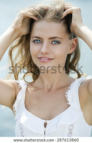 Close up Portrait, Young beautiful blonde woman in green dress posing outdoors in sunny weather - stock photo