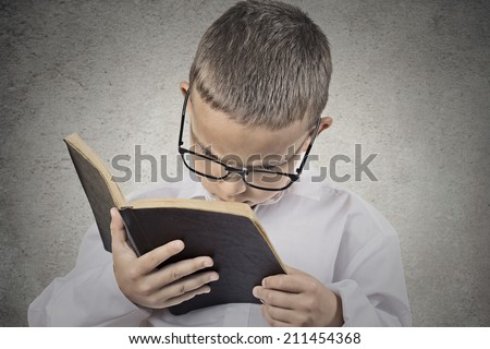 Close up portrait young, little man with glasses holding, reading old book, having difficulty to see text isolated grey wall background. Face expression. Education concept. Vision problems in children - stock photo