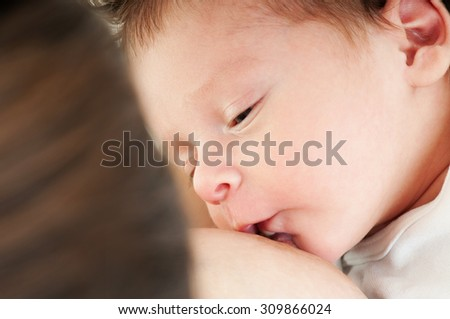 Close-up portrait. Young mother breastfeeds her baby. Breast-feeding.