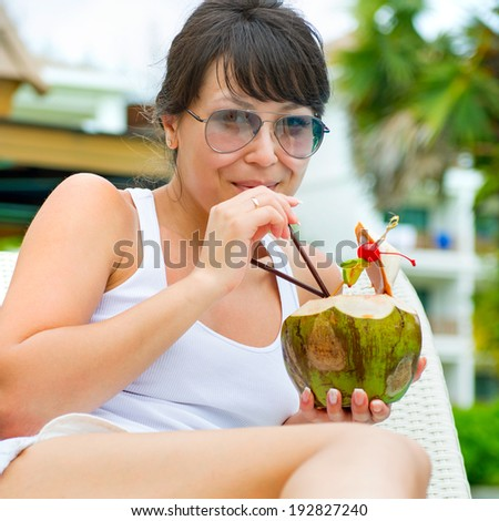 Close-up portrait young pretty woman drinking coconut cocktail against outdoor pool - stock photo