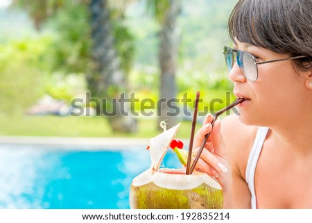 Close-up portrait young pretty woman drinking coconut cocktail against outdoor pool. Side view. Concept photo recreation and tourism