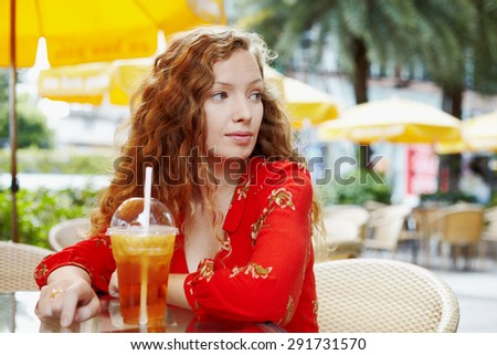 Close up portrait young woman sitting in outside cafe with cup of drink - stock photo