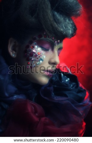 Close up portrait young woman with bright fantasy make up over red background - stock photo