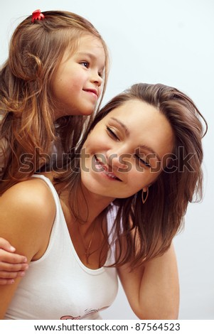 close-up portreit of happy smiling daughter hugging beautiful mother - stock photo