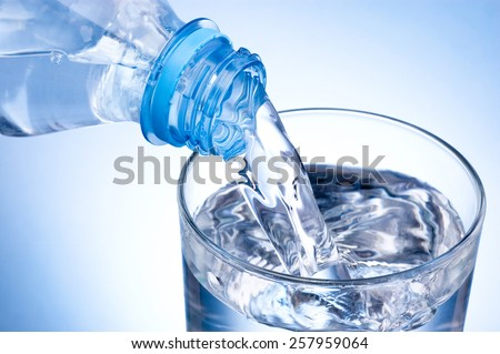 Close-up Pouring glass of water from a plastic bottle on blue background - stock photo