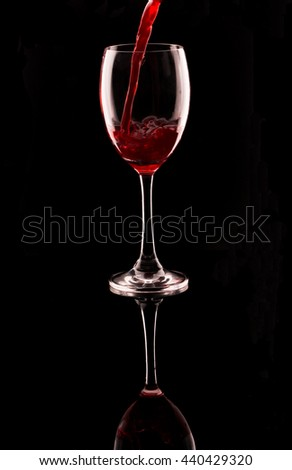 close up pouring red wine into the glass , black isolate - stock photo