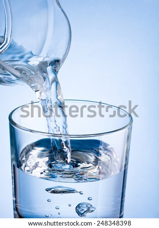 Close-up pouring water from a jug into glass on a blue background - stock photo