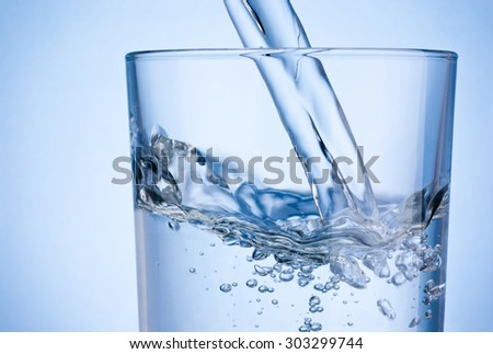 Close-up pouring water into glass on blue background - stock photo