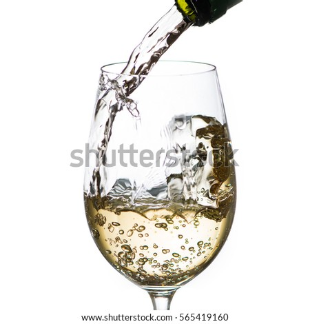 close up pouring white wine in glass, backlit