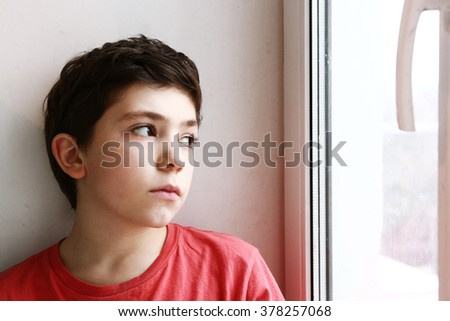 close up preteen boy portrait look at the window serious lonely sad expression - stock photo