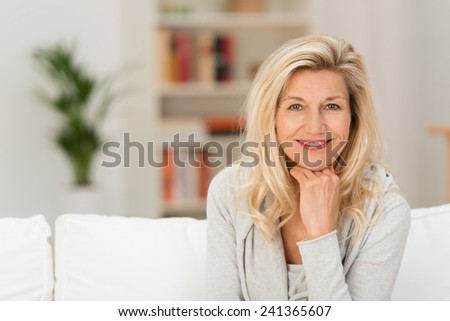 Close up Pretty Adult Woman Sitting on White Sofa with Hand on the Chin. Captured her While Looking at the Camera.