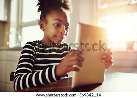 Close up Pretty Black Girl Watching Movie on her Tablet Computer at the Table Inside Home. - stock photo