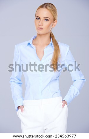 Close up Pretty Blond Woman in Light Blue Long Sleeve Blouse and White Pants. Looking at the Camera on Gray Background.
