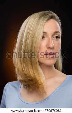 Close up Pretty Blond Young Woman in Casual Shirt, Looking Into Distance Seriously. Captured in Studio with a Brown Gradient Background.