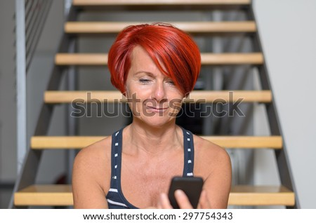 Close up Pretty Face of an Adult Redhead Woman Texting on Mobile Phone and Smiling Against Blurry Stairs.