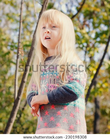 Close up Pretty Little Girl, with Long Blond Hair, Wearing Autumn Fashion Outfit at the Woodland with Tall Trees Background. - stock photo