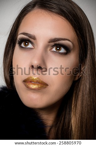 Close up Pretty Long Hair Young Woman with Gold Lips Make up Looking Up on a Gray Background - stock photo