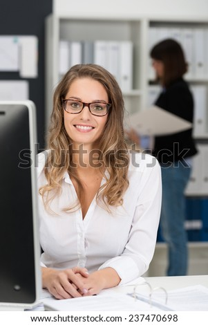 Close up Pretty Office Girl in White Long Sleeve Shirt and Eyeglasses, Looking at the Camera While Sitting at her Worktable. - stock photo