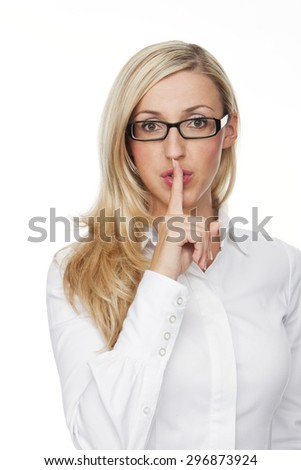 Close up Pretty Young Blond Woman with Eyeglasses, Showing Shushing Gesture at the Camera Against White Background. - stock photo