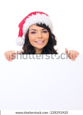 Close up Pretty Young Female Teen Santa Hat Behind White Big Board. Looking at Camera. - stock photo