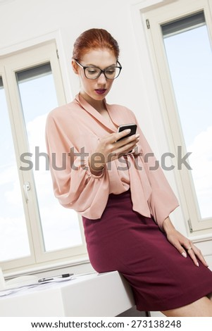 Close up Pretty Young Office Woman in Fashionable Business Attire Looking at her Mobile Phone While Sitting on the Table. - stock photo