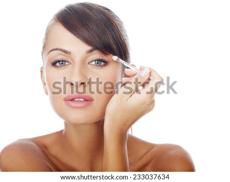 Close up Pretty Young Topless Woman with Sexy Pouting Lips Applying Eye Shadow Make- up While Looking at the Camera. Isolated on White Background. - stock photo
