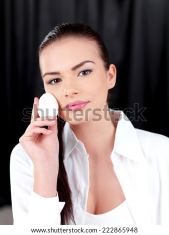 Close up Pretty Young Woman in White Attire Holding Face Powder Puff. Looking at Camera. Isolated on Black Curtain Background. - stock photo
