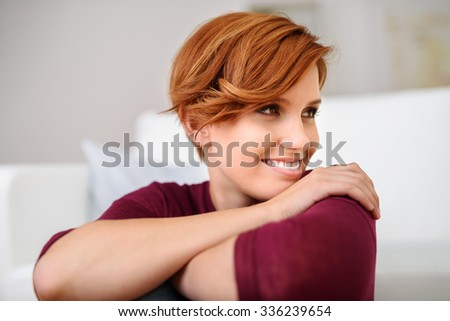 Close up Pretty Young Woman Resting her Chin on Hand and Looking to the Right of the Frame with Happy Facial Expression. - stock photo