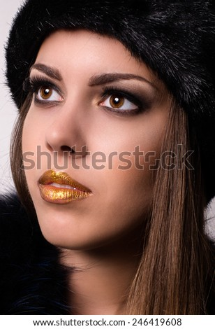 Close up Pretty Young Woman with Gold Lips Make-up, Wearing Winter Fur Hat While Looking Up. - stock photo