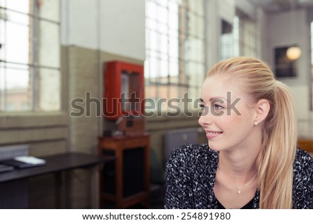 Close up Pretty Young Woman with Ponytail Blond Hair Facing Left Frame with Smile on her Face. - stock photo