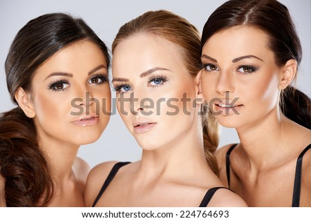 Close up Pretty Young Women Faces  Looking at Camera. Captured in Studio on Gray Background.