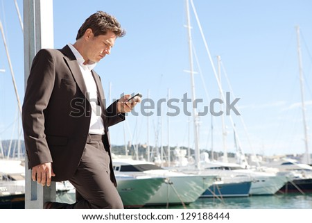 "Close up profile of a businessman using his ""smart phone"" while standing near a marine with luxury yachts against a deep blue sky and sea. - stock photo"