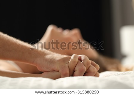 Close up profile of a couple having sex on a bed at home in the night - stock photo