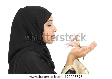 Close up profile of an Arab woman smelling a flower, isolated on a white background. - stock photo