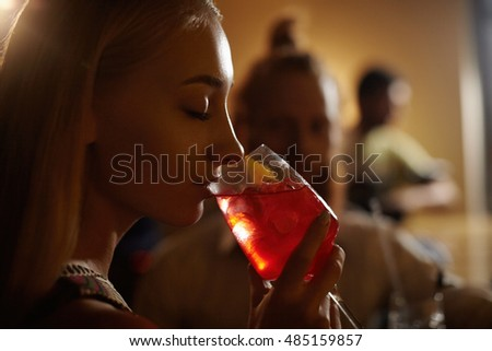 Close-up profile of glamorous blonde girl enjoying fresh fruit drink, sitting at bar counter next to her redhead boyfriend. Young woman drinking cocktail with closed eyes. Selective focus on glass
