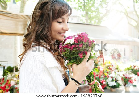 Close up profile portrait of a beautiful and young woman enjoying and smelling a bouquet of flowers while standing in a fresh floral market stall during a sunny day outdoors.