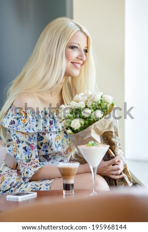 Close up profile portrait of a beautiful and young woman enjoying and smelling a bouquet of flowers while standing in a fresh floral market stall during a sunny day outdoors. - stock photo