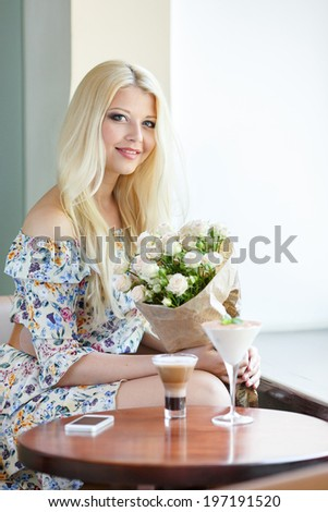 Close up profile portrait of a beautiful and young woman enjoying and smelling a bouquet of flowers while standing in a fresh floral market stall during a sunny day - stock photo