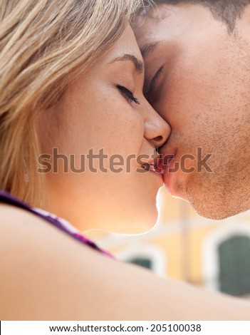 Close up profile portrait of an attractive young couple being romantic and passionately kissing during a summer break vacation on a hot day. First love and relationships lifestyle, outdoors. - stock photo